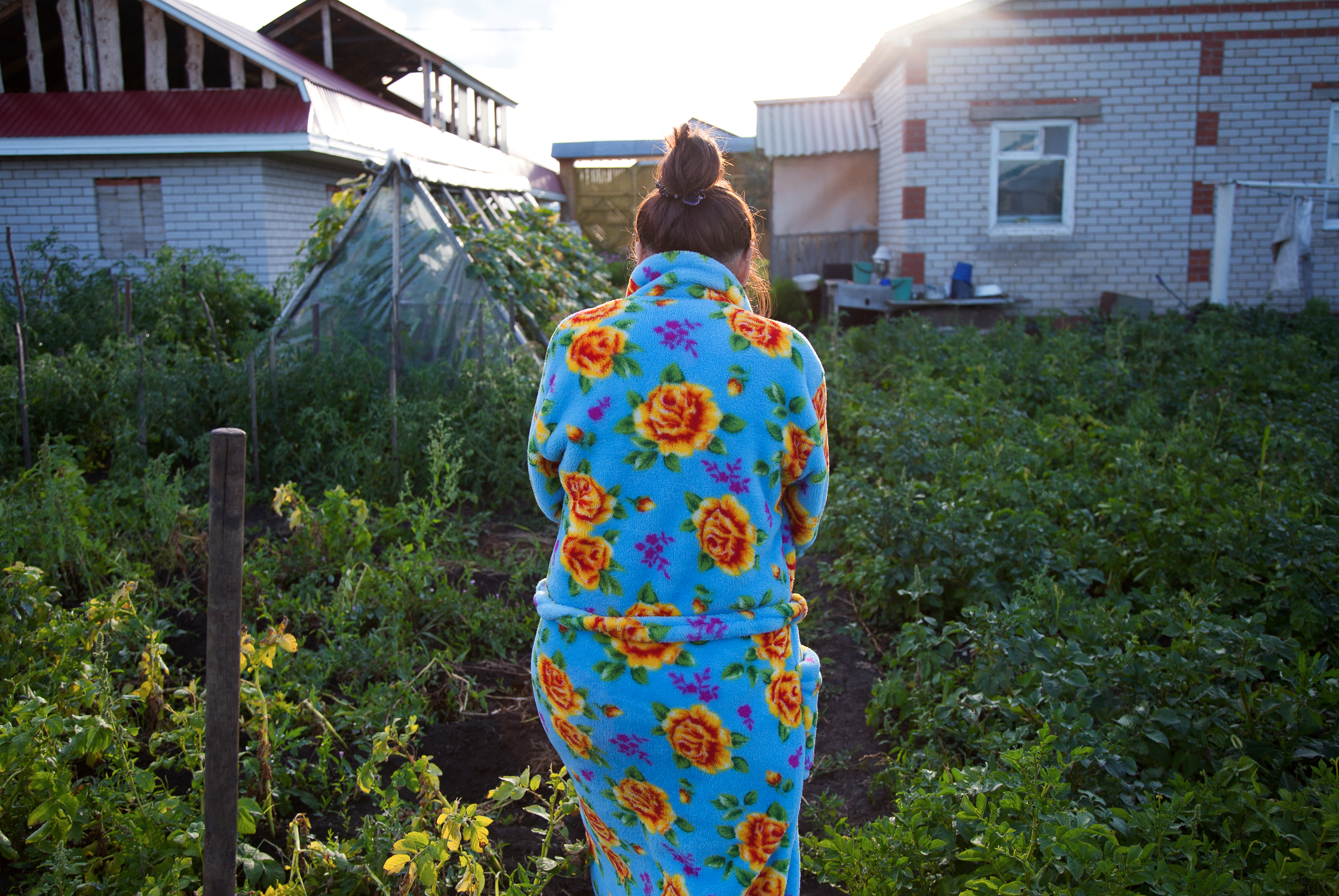 Zila Idrisova walks through her brother's garden in the village of Aktanish.